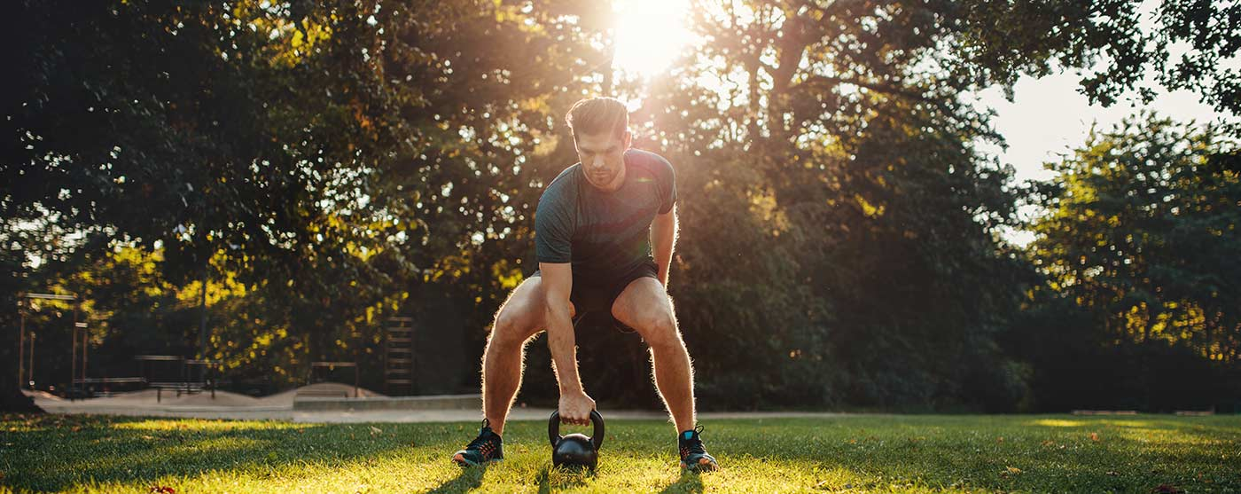 Man exercising with kettlebell outside
